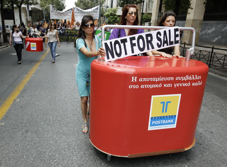Des employées de la banque Hellenic pousse un guichet fictif pour protester contre le plan de privatisation d'une partie des entreprises publiques grecques. Photo le 2 juin 2011 à Athènes.