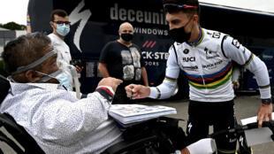 Le Français champion du monde Julian Alaphilippe (Deceuninck) signe des autographes à ses supporters, le 24 juin 2021 à Brest, ville du grand départ du Tour de France
