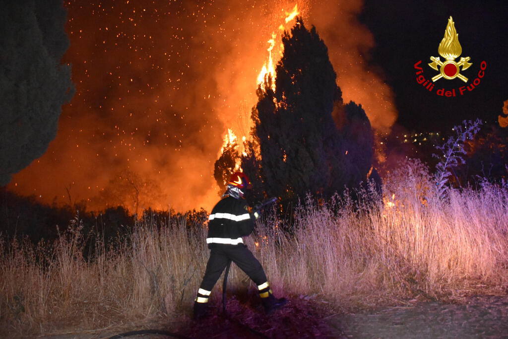 """Italian firefighters, """"Vigili del Fuoco,"""" battle a blaze raging around Palermo, Sicily, that has forced people from their homes."""