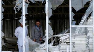 Dos hombres miran a través de los cristales rotos de una ventana  en el lugar donde se produjo un atentado suicida en Kabul.