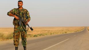 Un membre des forces armées syriennes sécurise une route près de la frontière avec l'Irak, le 10 mai 2017.