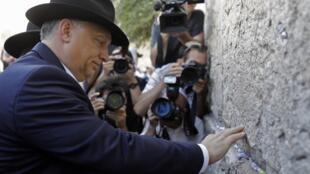 Con un sombrero negro en honor a la tradición judía que obliga a los hombres a taparse la cabeza, Orban, acompañado del rabino Shmuel Rabinowitz, deslizó una nota en una de las grietas del Muro de los Lamentos.
