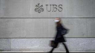 Una viandante con mascarilla pasa frente a la sede central del banco suizo UBS, el 3 de marzo de 2021 en la ciudad suiza de Ginebra