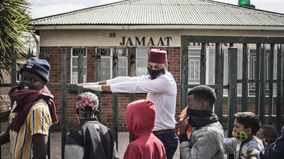 Rashad, bénévole de l'association caritative Hunger has no religion demande aux enfants de faire la queue pour maintenir une distance sociale à Johannesburg, le 25 mai 2020, lors d'un repas de l'Aïd al-Fitr à Westbury et Coronationville.