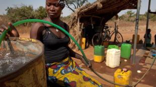 Une femme dans le village de Badnoogo, au Burkina Faso, collecte de l'eau propre.