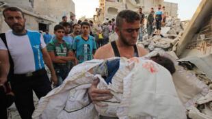 Un homme syrien porte le corps d'un enfant tué dans une attaque aérienne du gouvernement sur le district rebelle Al-Maghair de la ville d'Alep, au nord de Syrie, le 16 septembre 2015.