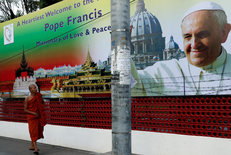 Một nhà sư đi qua một tấm áp phích cỡ lớn có ảnh giáo hoàng Phanxicô, tại Rangoon, Miến Điện, ngày 26/11/2017.