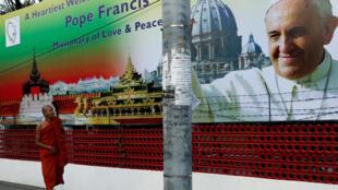 Katika mji wa Rangoon, mji mkuu wa Burma, kiongozi wa Wabuddha apita karibu na bango lililo na pich ya Papa Francis, ambaye anataraji kuzuru nchi hiyo leo Jumatatu Novemba 27, 2017.