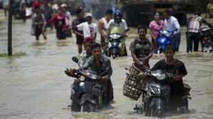 Les résidents traversent une route inondée dans la ville de Taungnu, dans la région de Bago, le 31 août 2018.