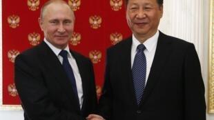 El presidente ruso Vladimir Putin (I)  estrecha la mano de su par chino t Xi Jinping durante una reunión en el Kremlin, en Moscú, Rusia, el 3 de julio de 2017.