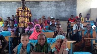 Teacher Gassah Youdas and class at Espoir 1 school, Dar es Salaam, Lake Chad