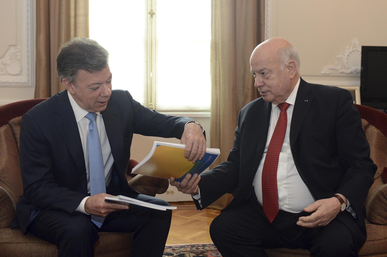 El presidente colombiano, Juan Manuel Santos, recibe el texto de la OEA sobre las drogas de manos del Secretario General del organismo, José Miguel Insulza, Bogotá, 17 de mayo de 2013.