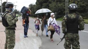 Bajo la vigilancia de soldados colombianos, los migrantes venezolanos parten a pie hacia la frontera venezolana después de un cierre ordenado por el gobierno en un esfuerzo por prevenir la propagación del nuevo coronavirus, en Bogotá, Colombia, el lunes 6 de abril de 2020. Muchos venezolanos en Colombia dicen que no han podido encontrar trabajo en un país donde los negocios permanecen cerrados y se ha ordenado a la gente que se quede dentro.