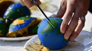 Ambientalista a cortar uma laranja pintada como o planeta Terra para simbolizar o dia em que a humanidade usou mais recursos naturais do que aqueles que o planeta consegue renovar por ano. Berlim. 1 de Agosto de 2018.