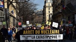 "Environmental activists hold a banner reading ""Stop nuclear power, let's not wait for disaster!"" during a demonstration organised by Greenpeace and other groups to mark the 6th anniversary of the Fukushima nuclear disaster, on March 11, 2017 in Paris."