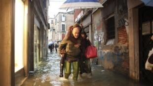 Turistas paseando por una calle inundada, 11 noviembre 2012.
