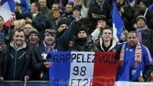 """Fans da seleção francesa com cartaz dizendo:""""lembrem 98... e 1 e 2 e 3 a 0"""""""