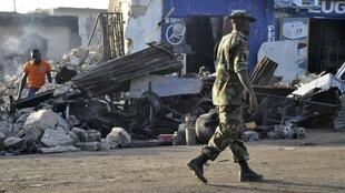 A soldier walks past the scene of a bomb explosion in Nigeria's northern city of Kaduna