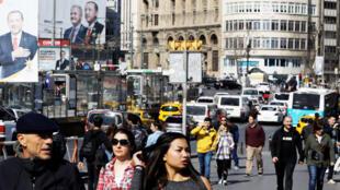 Les gens marchent le long du pont de Galata, sous les bannières du président turc Tayyip Erdogan et du candidat du parti AKP à la mairie d'Istanbul, Binali Yildirim, lors des prochaines élections locales. Istanbul, en Turquie, le 25 mars 2019.