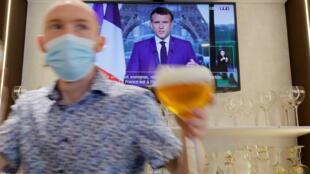 Le discours d'Emmanuel Macron diffusé sur la télévision d'un bar à Cambrai. 12 juillet 2021.