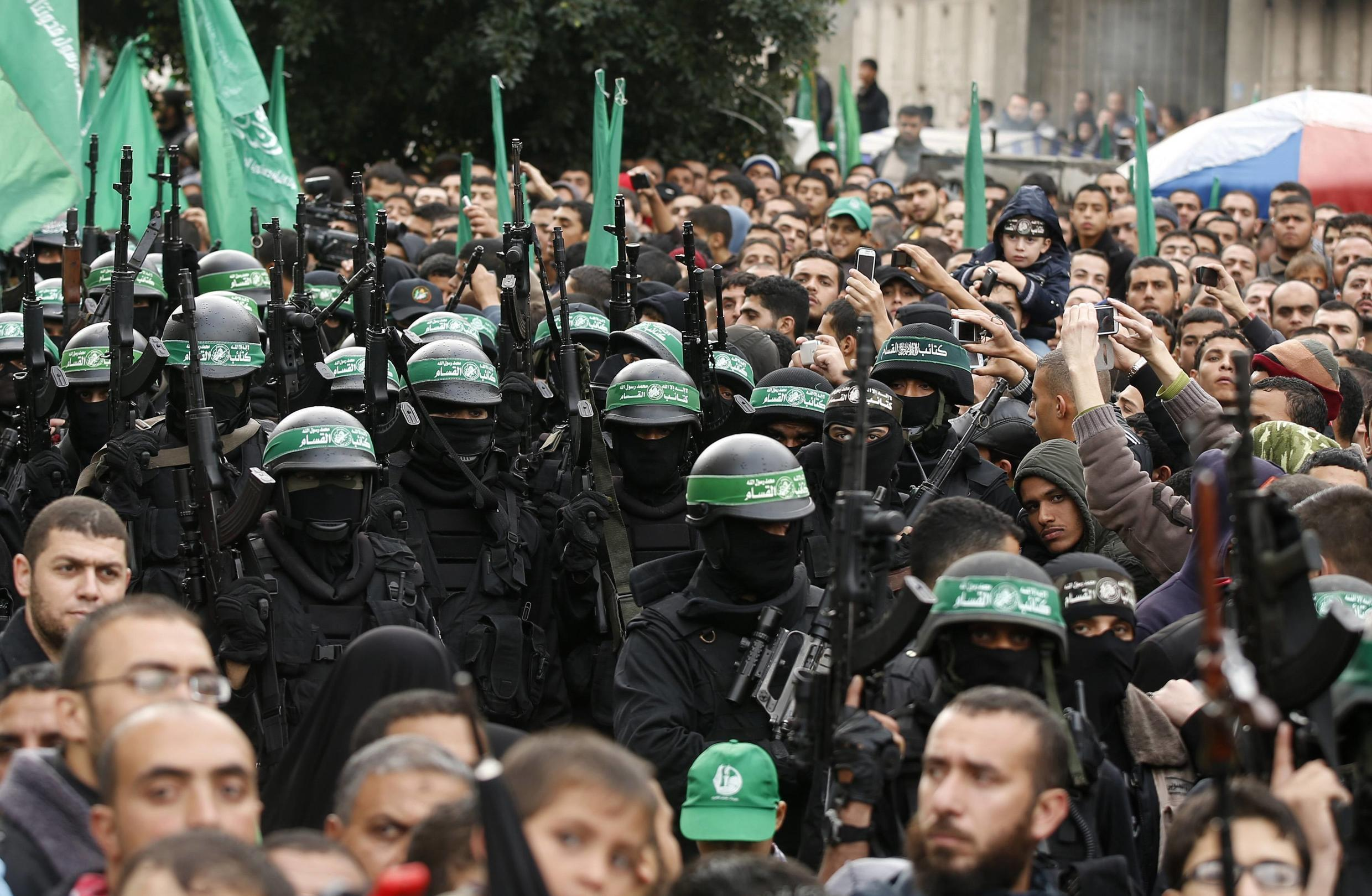 Gazans watch members of the Ezzedine al-Qassam Brigades take part in a military parade marking the 27th anniversary of Hamas's founding
