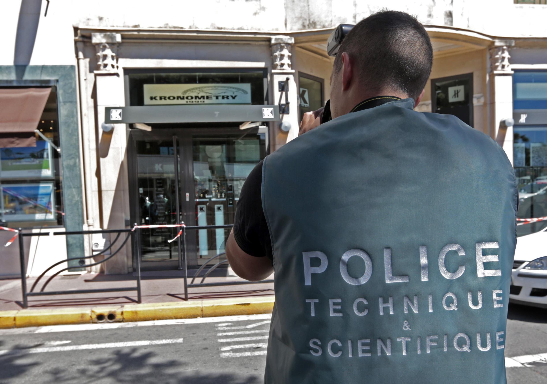 Член экспертной бригады полиции перед магазином Kronometry после ограбления. Канны 31/07/2013