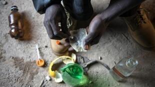 Sur cette photo prise le 17 juillet 2015, un dépendant du cocktail de drogue connu localement sous le nom de Nyaope (Nyope) se prépare à s'injecter de la drogue dans un bâtiment abandonné du township de Simuneye à la périphérie de Johannesburg.