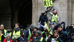 Un gilet jaune tient un carton portant l'inscription «référendum d'initiative citoyenne  - RIC» lors d'une manifestation contre la hausse du coût de la vie, devant l'Opéra de Paris, le 15 décembre 2018.