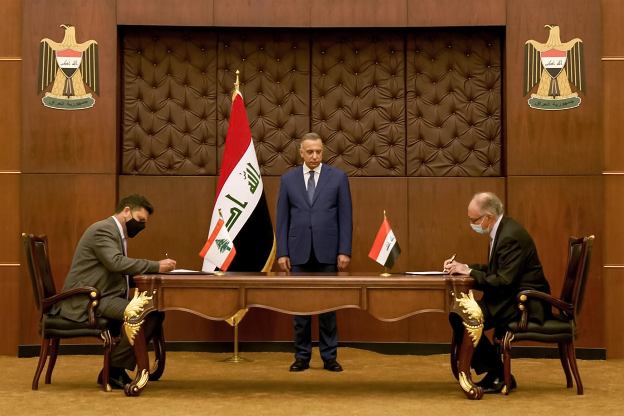 Iraqi Prime Minister Mustafa al-Kadhemi (C) looks on as Lebanon's energy minister Raymond Ghajar (L) and Iraq's Finance Minister Ali Allawi (R) sign bilateral agreements in the capital Baghdad