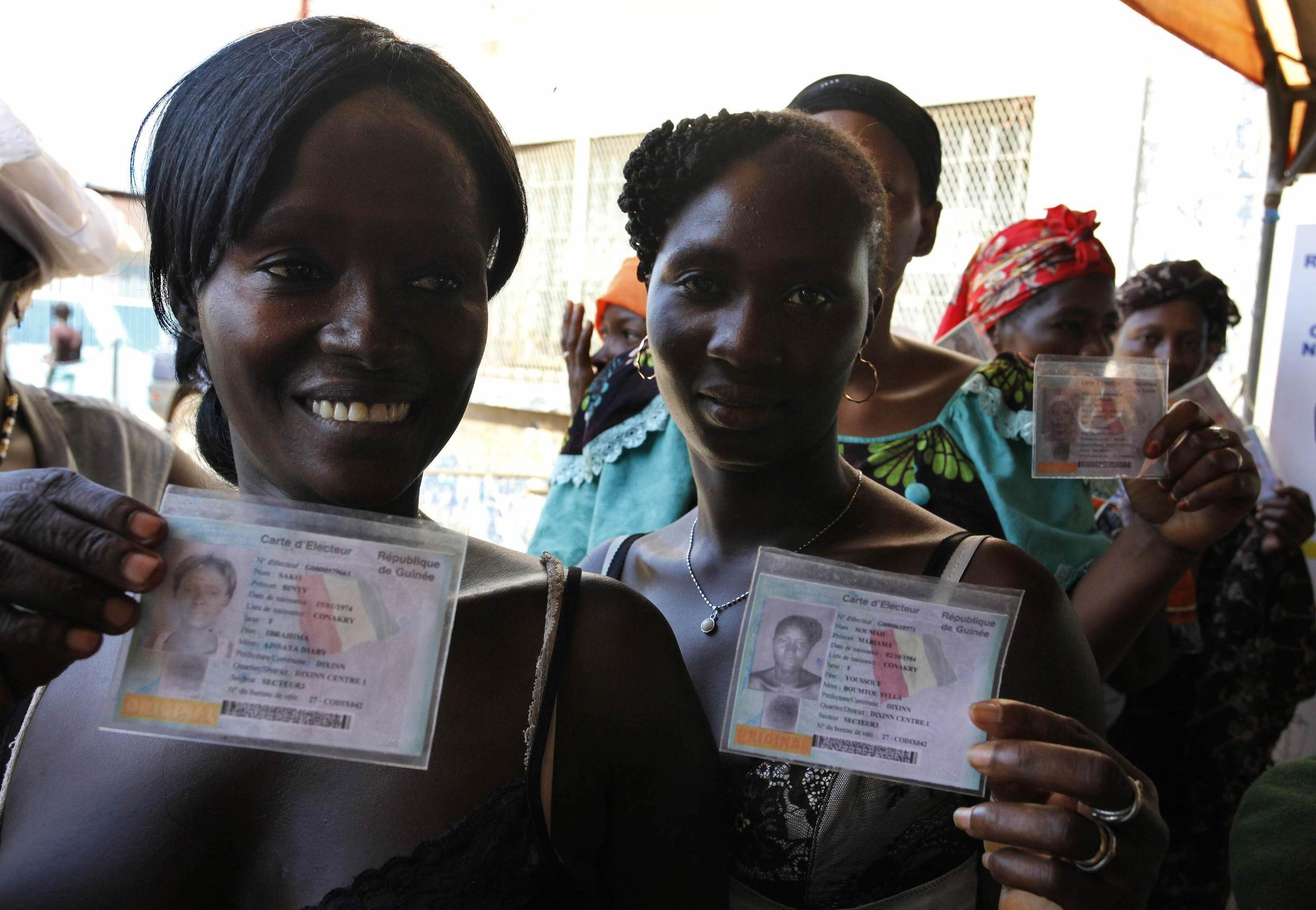 Voters show their voting cards as they wait in line at a polling station ni Conakry