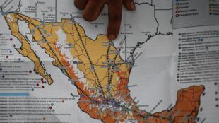 Un hombre señala en un mapa mientras la caravana de migrantes va de México a la frontera con Estados Unidos, el 21 de octubre de 2018 en Tapachula.