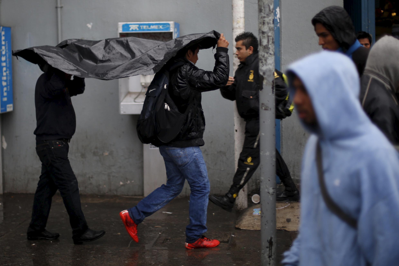 Moradoes de Guadalajara se protegem das fortes chuvas provocadas pelo furacão Patricia, que perdeu força ao entrar no México.