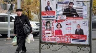 Des passants devant des affiches de candidats aux élections législatives anticipées, à Erevan le 6 décembre 2018.