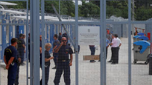 Des agents de sécurité se tiennent près de l'entrée de la zone de transit où les migrants sont hébergés dans des conteneurs, à Tompa, en Hongrie, le 14 juin 2017.
