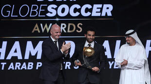 FIFA President Gianni Infantino hands Mohamed Salah the best Arab player of the year award during the Dubai Globe Soccer Awards Ceremony in Dubai