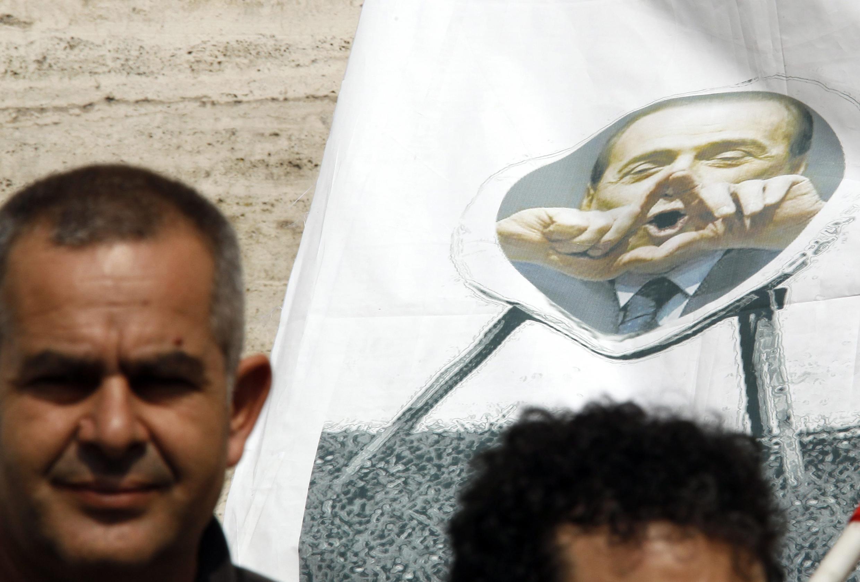 Manifestante carrega banner com imagem de Silvio Berlusconi durante protesto contra medidas de austeridade na Itália.