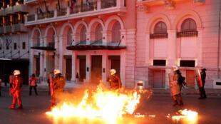Policias tentam controlar bombas lançadas por manifestantes, em Atenas.
