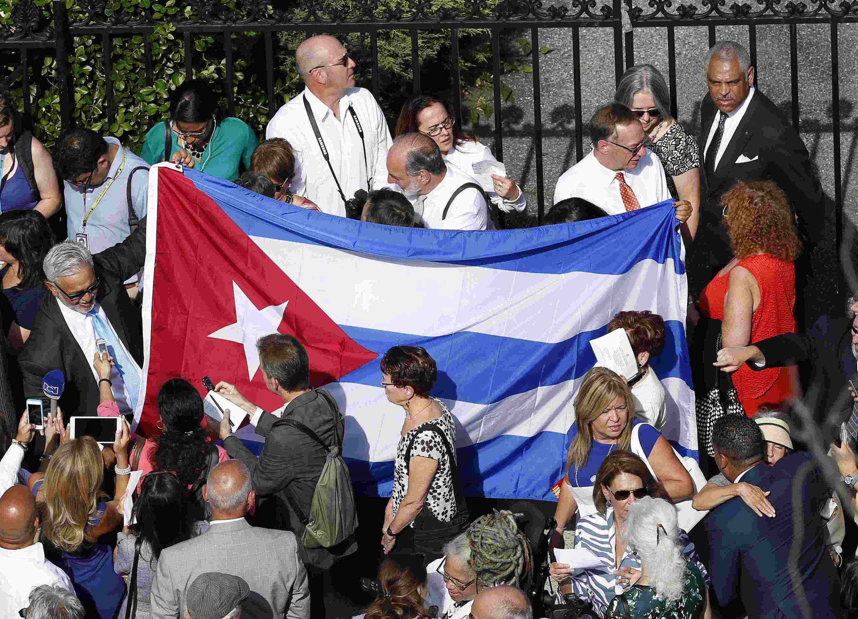 Bendera ya Cuba ikinyanyuliwa na umati wa watu mbele ya Ubalozi wa Cuba kabla ya kufunguliwa upya mjini Washington Julai 20, 2015.