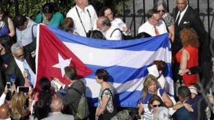Le drapeau cubain est brandi par la foule située devant l'ambassade de Cuba avant sa réouverture à Washington, le 20 juillet 2015.