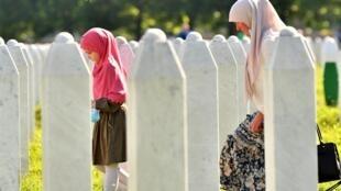 Une musulmane bosniaque, survivante du massacre de Srebrenica en 1995, et sa petite-fille marchent entre les pierres tombales du cimetière commémoratif de Potocari, un village juste à l'extérieur de Srebrenica, le 11 juillet 2020.