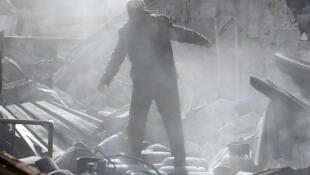 (Ảnh minh họa) - Một thường dân Syria đứng trên đống đổ nát sau một trận oanh kích ngày 26/11/2017.