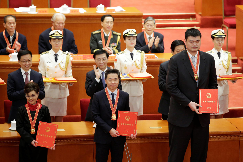 Robin Li, au milieu, en compagnie de la chanteuse Li Guyi et de l'ancien basketteur Yao Ming, tous trois médaillés pour marquer les 40 ans de l'ouverture de la Chine à l'économie de marché.