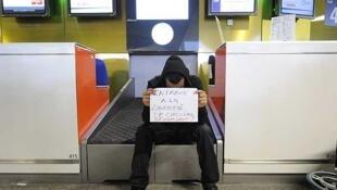"""Un hombre en el aeropuerto francés de Roissy sostiene un cartel que reza: """"Una traba a la libertad de circular.  ¿Con qué derecho?""""."""