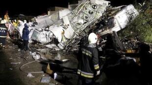 消防人员在台湾复兴航空公司GE222班机坠机处奔忙救援  2014年7月23日台湾澎湖