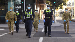 Soldiers help police officers patrol the streets of Melbourne, Australia, as the city re-entered lockdown against Covid-19, 2 August 2020.