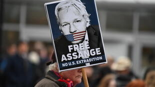 Un simpatizante de Julian Assange sostiene un cartel a favor de su liberación y en contra de su extradición a EEUU, el 24 de febrero de 2020 ante un juzgado al sureste de Londres