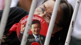 Un supporter des «chemises rouges» tient un évantail à l'effigie de l'ancien Premier ministre thaïlandais, Thaksin Shinawatra.