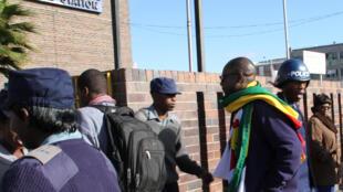 Le pasteur Evan Mawarira, le drapeau zimbabwéen autour du cou, à son arrivée au commissariat de police à Harare, le 12 juillet 2016.