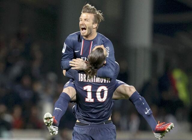 David Beckham salta nos braços de Zlatan Ibrahimovic para festejar a vitória do Paris Saint-Germain.