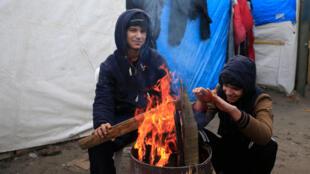 Dois adolescentes originários do Kuwait se aquecem em fogueira no acampamento de migrantes de Calais, no norte da França.